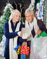 Senior Couple Using Digital Tablet At Christmas Store