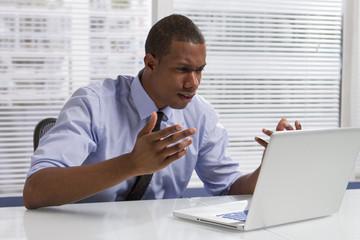 African American businessman upset at computer, horizontal