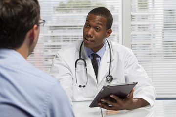 Doctor with patient and holding tablet, horizontal