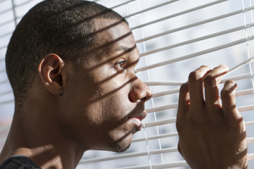 Nervous young black man looking out window, horizontal