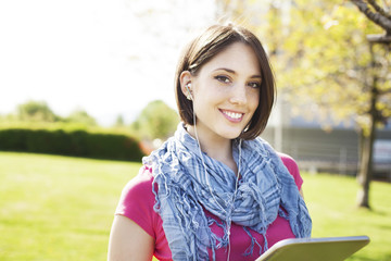 Young woman standing on grass listening to music and enjoying