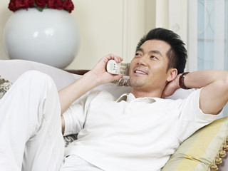 asian man talking on phone at home