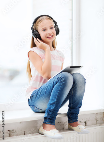 girl with tablet pc and headphones at home