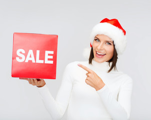 woman in santa helper hat with red sale sign