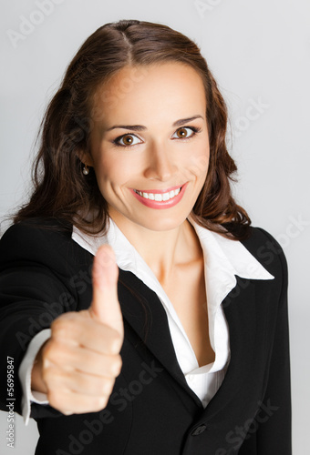 Businesswoman with thumbs up, over gray