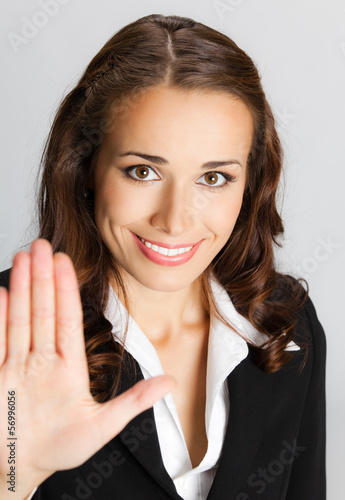 Businesswoman with stop gesture, over gray