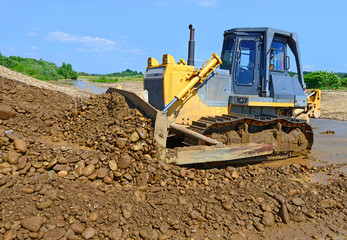 The bulldozer performs works in the tideway of  river