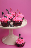 Female high heel shoes on pink and black cupcakes