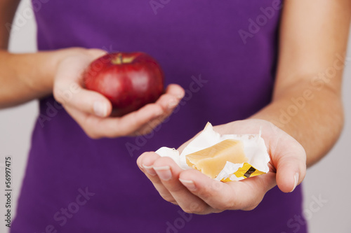 Young woman holding candy and apple