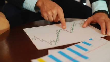 Business people analyze financial charts