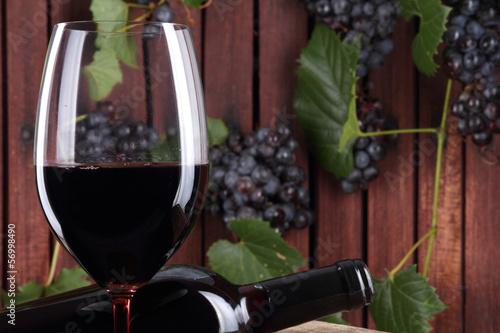 vino rosso nel bicchiere con bottiglia e grappoli d'uva
