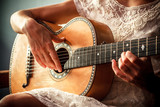Young woman playing guitar indoors on sunny day