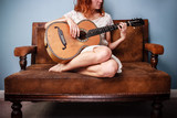 Beautiul young woman on sofa is playing guitar