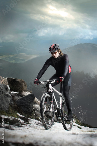 Cyclist climbing on a rock