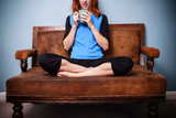 Young woman in relaxed pose is drinking tea on old sofa