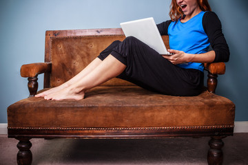 Happy young woman sitting on sofa using her laptop