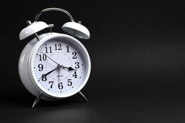 White vintage alarm clock against black background