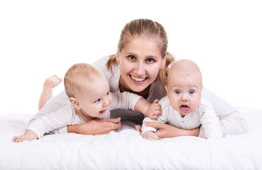 Smiling young woman with two baby boys over white