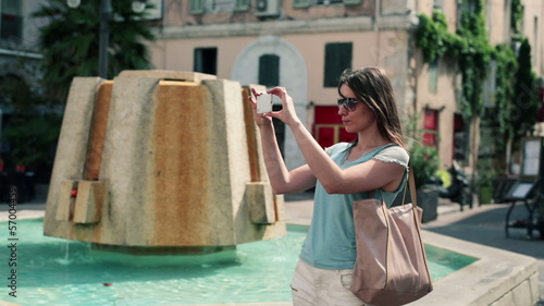 Woman taking photo with cellphone in the city