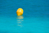 Yellow buoy floating in Mediterranean turquoise sea