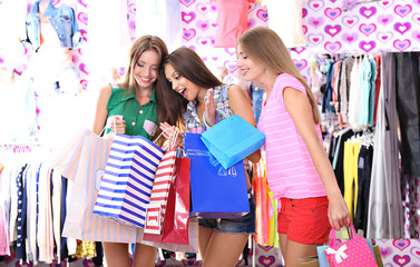 Three beautiful young woman in shop with shopping bags
