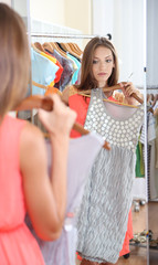 Beautiful girl trying dress near mirror on room background