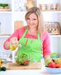 Happy smiling woman in kitchen preparing vegetable salad