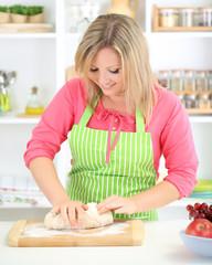 Woman kneads dough