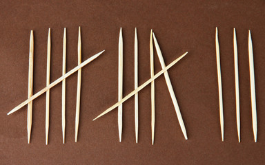 Toothpicks - counting days concept on brown background