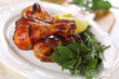 Roast chicken legs with lemon and herbs on plate.
