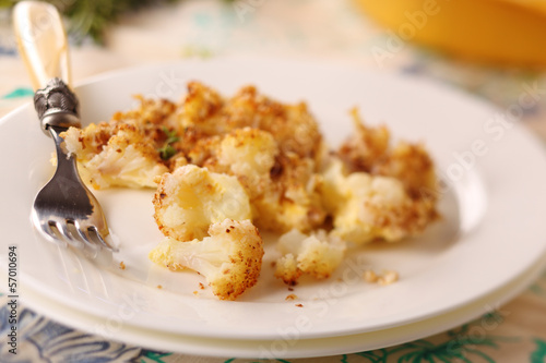 Baked cauliflower with cheese and nuts on a plate.