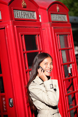 Woman on smartphone by London red phone booth