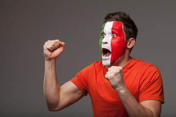 Footbal fan is rooting. With painted Italian flag on a face