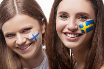Two girls with painted flags on their face.