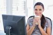 Happy attractive businesswoman having coffee