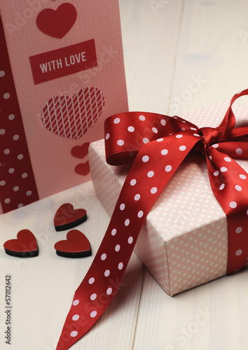 Love theme pink and red gift with card on shabby chic table.
