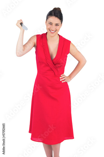 Smiling elegant brunette in red dress holding knife