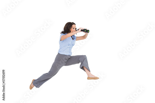 Cheerful classy businesswoman jumping while holding binoculars