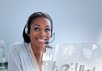Cheerful woman with headset using futuristic interface hologram