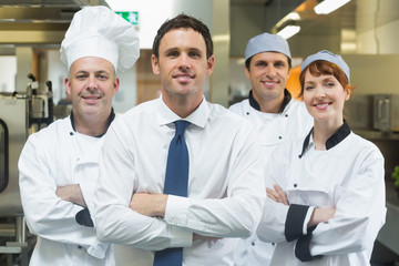 Restaurant manager standing in front of team of chefs
