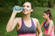 Cute fit woman wearing sportswear drinking water