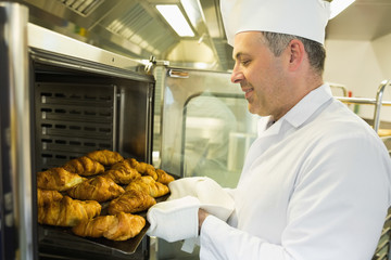 Mature baker putting some croissants into an oven