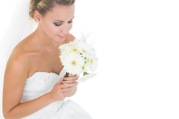 Side view of beautiful bride looking at her bouquet