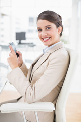 Happy smart brown haired businesswoman using a mobile phone