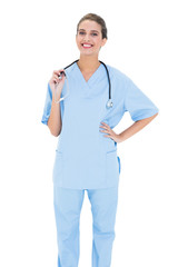 Happy brown haired nurse in blue scrubs looking at camera
