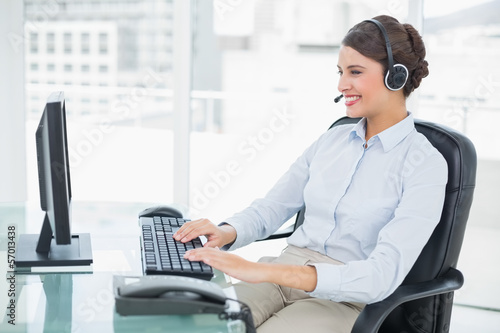 Cheerful classy brown haired operator using her computer