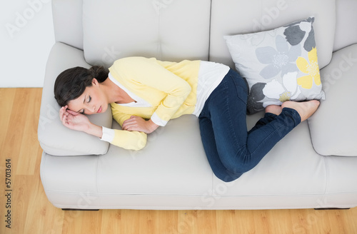 Peaceful casual brunette in yellow cardigan sleeping on the couc