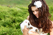 Young woman bride smiling and holding two cute rabbits over park