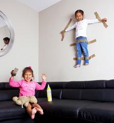 enfant bavard accroché au mur par sa soeur