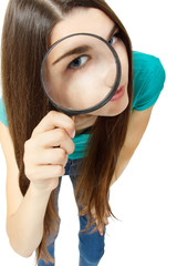 Attractive girl looking through a magnifying glass over white